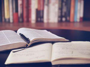 Studia z etyki - na fotografii widać rozłożoną książk, na której leży pióro. Pod książką rozłożony notes z notatkami. W tle widać półkę z książkami.